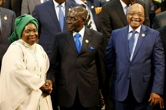 Chairperson of the African Union (AU) Commission Nkosazana Dlamini-Zuma smiles as she is greeted by Zimbabwe's President Robert Mugabe next to South Africa's president Jacob Zuma ahead of the 25th African Union summit in Johannesburg